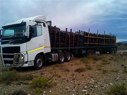 A bulk order of treated poles and droppers on a truck.